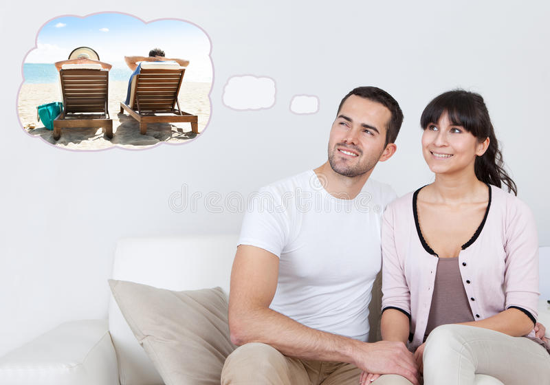 Par som drömmer av utgiftersemester på stranden royaltyfri foto