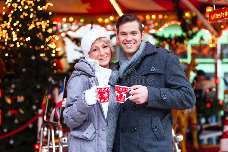 Par som dricker kryddat vin på julmarknad fotografering för bildbyråer