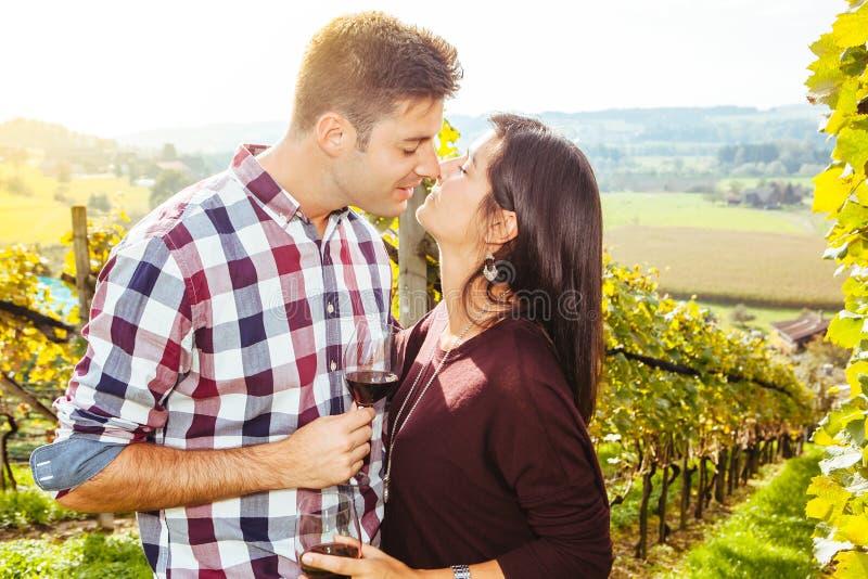 Par som dricker och kysser i en vingård royaltyfri bild