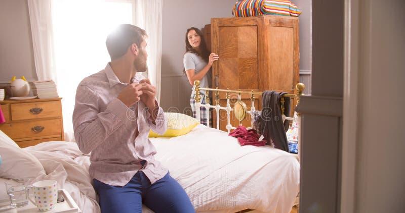 Par som får klädde för arbete i sovrum royaltyfri foto