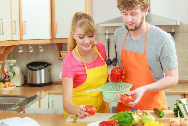 Par som förbereder matsallad för nya grönsaker royaltyfri bild