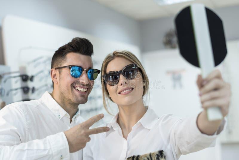 Par som försöker på solglasögon i optiskt lager royaltyfri bild