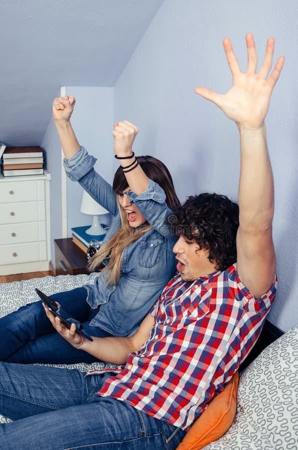 Par som firar den hållande ögonen på sporten för seger royaltyfri bild