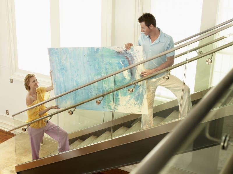 Par som flyttar modernt måla upp trappa royaltyfri foto