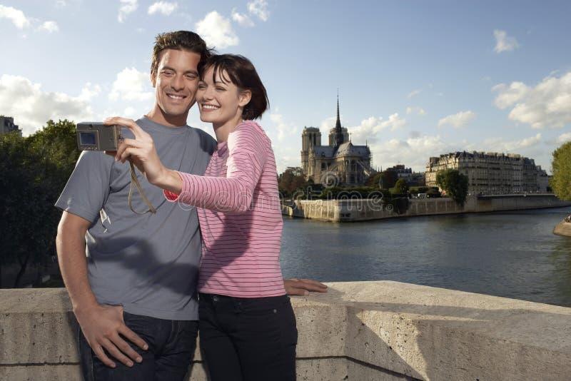 Par som fotograferar sig i Front Of Notre Dame Cathedral arkivbilder