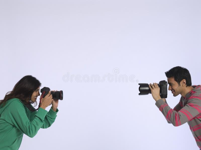 Par som fotograferar sig i studio royaltyfria bilder