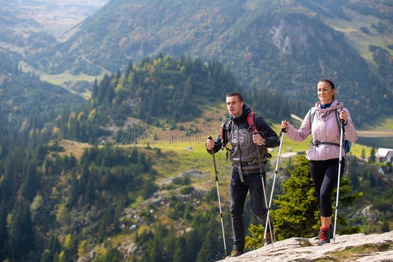Par som fotvandrar i berget och tycker om sikt på sjön arkivbilder