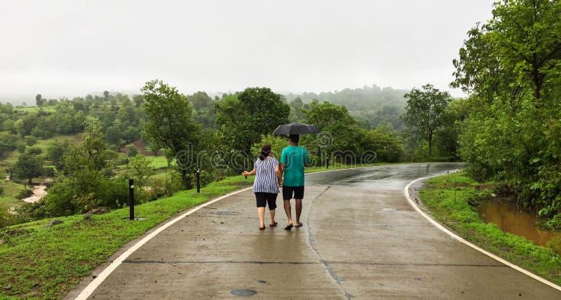 Par som går handen - i - hand under paraplyet i monsun royaltyfria foton