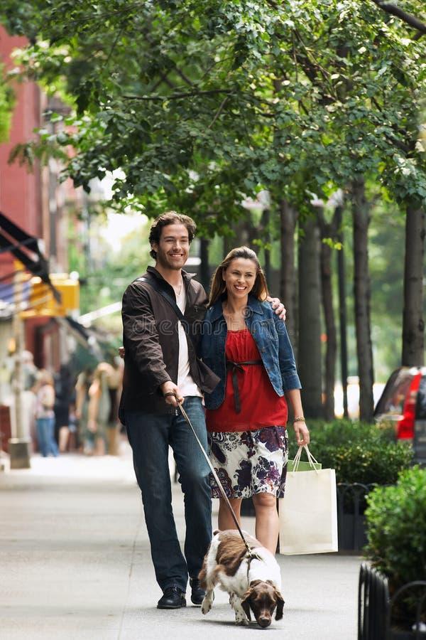 Par som går hunden på trottoaren royaltyfri fotografi