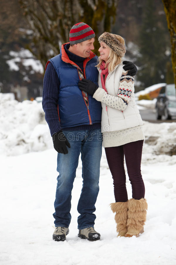 Par som går längs den snöig gatan skidar in, semesterorten royaltyfri foto