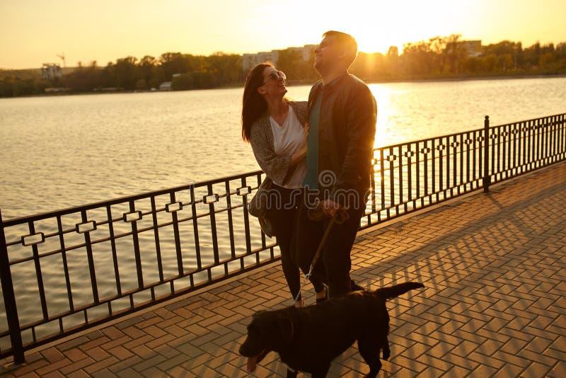Par som går med den älsklings- hunden vid sjön royaltyfria bilder