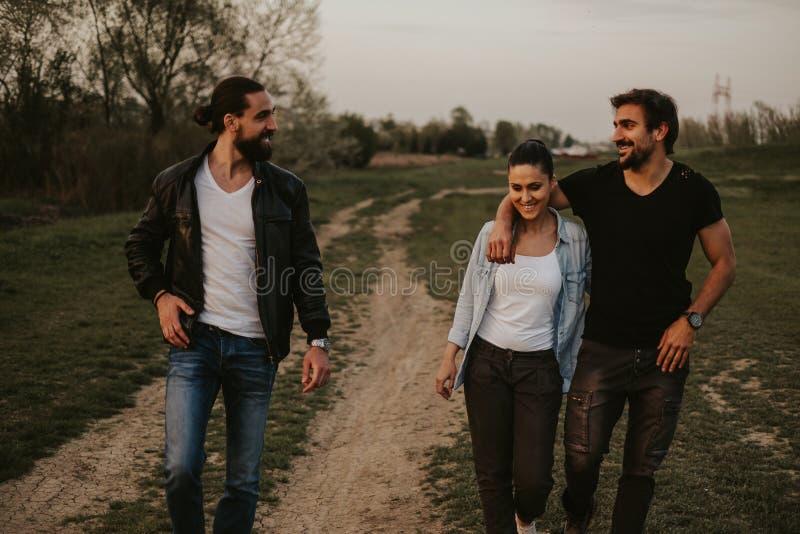 Par som går med vännen, i natur och att le arkivfoton