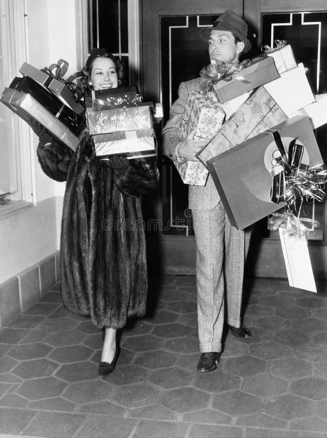 Par som går och rymmer buntar av gåvor (alla visade personer inte är längre uppehälle, och inget gods finns Leverantörwarranti arkivbild