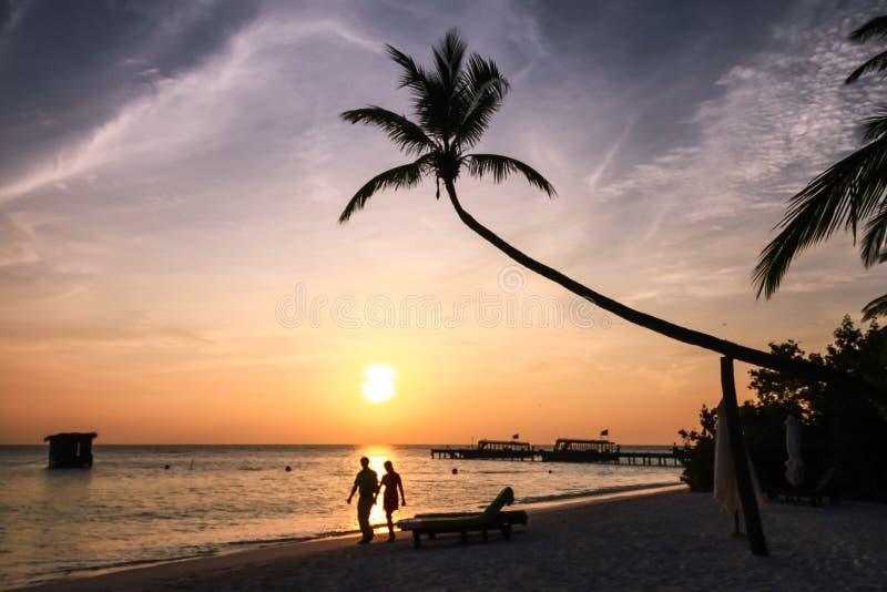 Par som går på den maldiviska stranden för ösemesterort på solnedgången arkivbilder