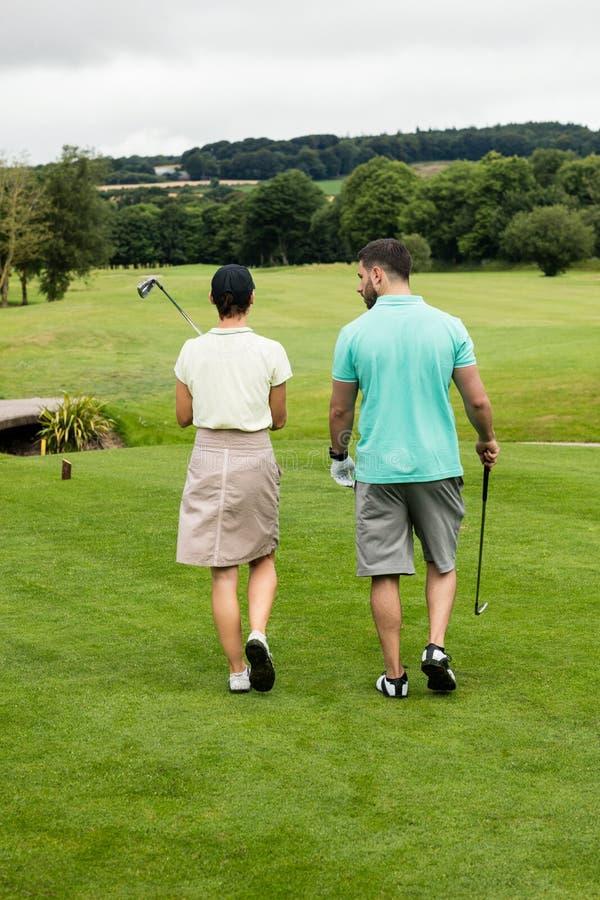 Par som går på en golfbana arkivbilder