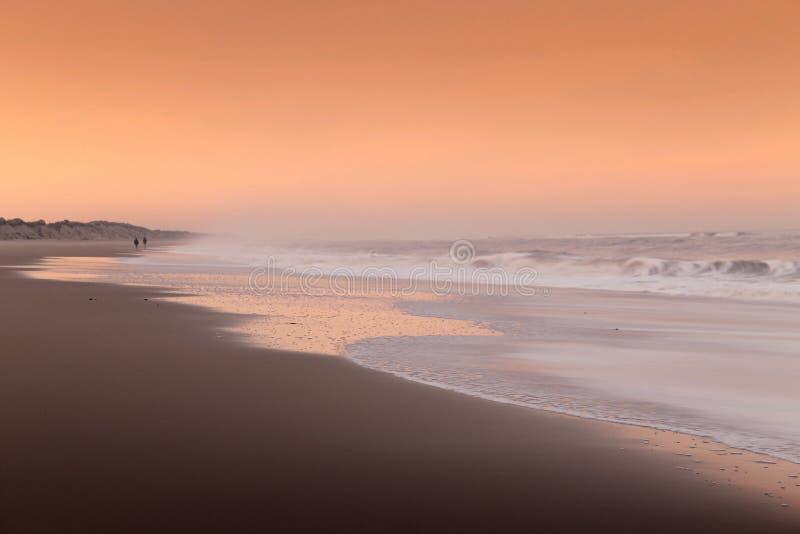 Par som går på en strand på solnedgången royaltyfri fotografi