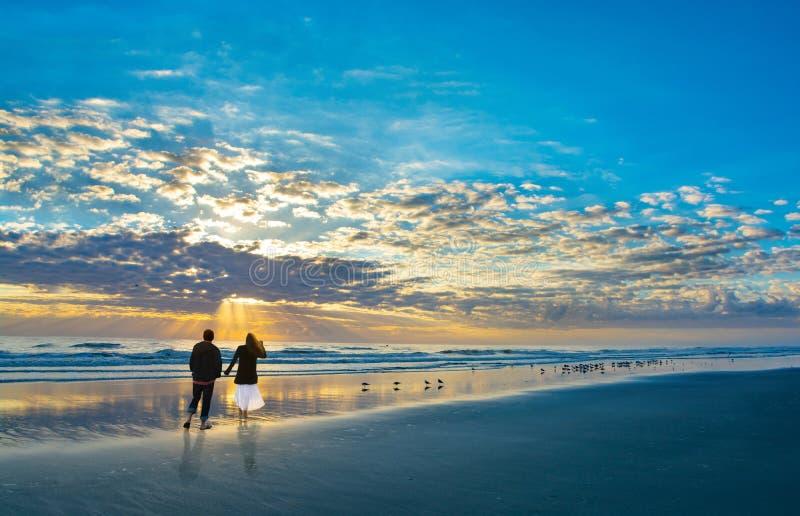 Par som går på stranden på soluppgång som tillsammans tycker om tid royaltyfria foton