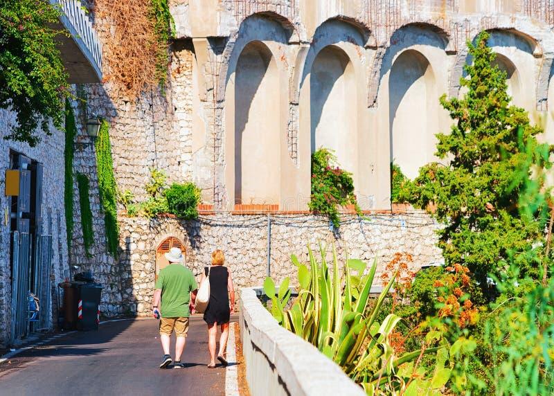 Par som går på vägen längs, vaggar i den Taormina semesterorten Sicilien arkivbilder