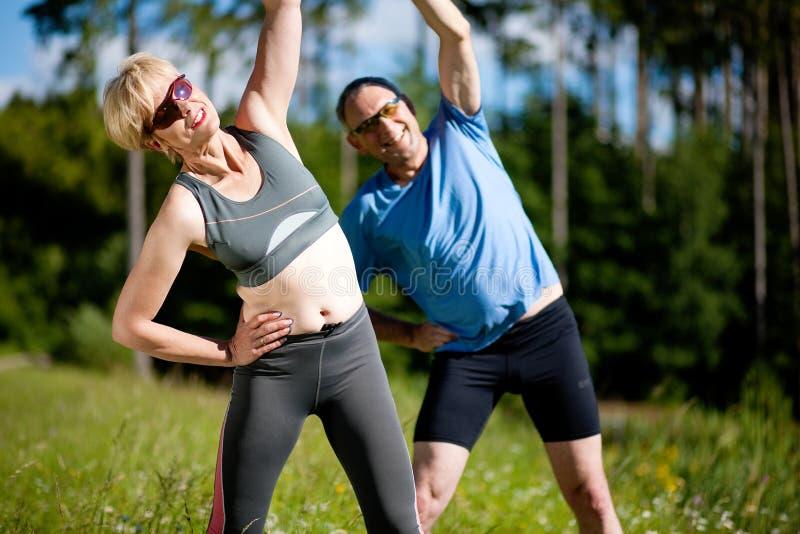 par som gör öva den utomhus höga sporten arkivfoto