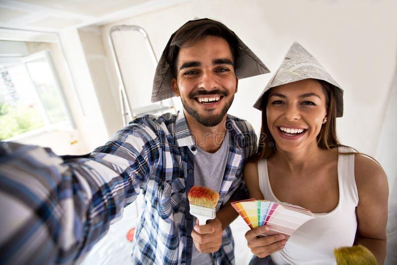Par som gör selfie, medan måla deras hem royaltyfri foto