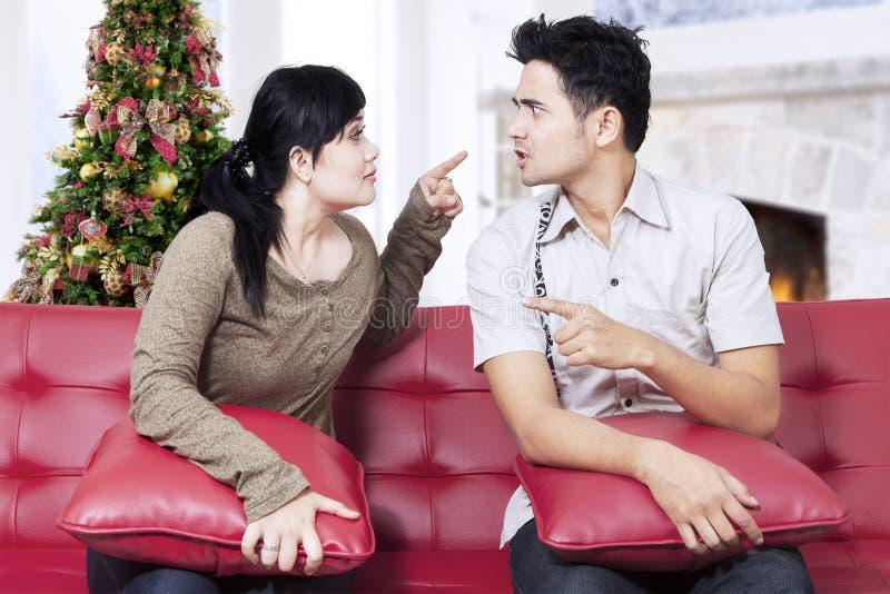 Par som grälar på soffan i juldag royaltyfria foton