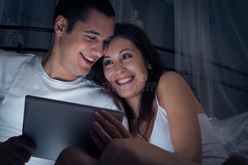 Par som håller ögonen på en video på deras minnestavladator arkivbilder