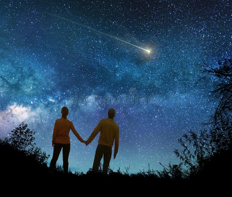 Par som håller ögonen på stjärnorna i natthimmel royaltyfri bild