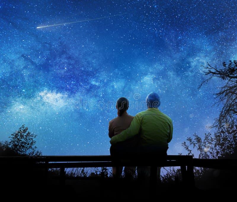 Par som håller ögonen på stjärnorna i natthimmel arkivbild