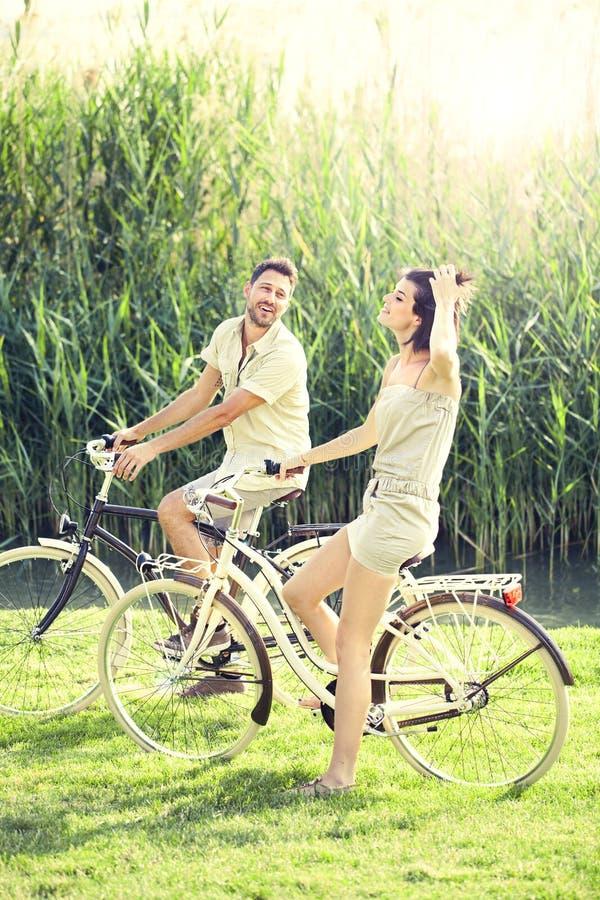 Par som har cyklar, rider in i naturen royaltyfri bild