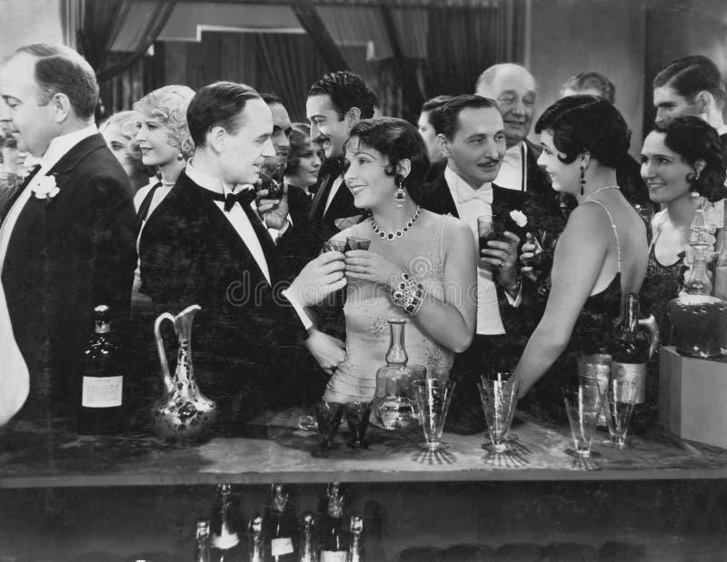 Par som har drinken på den fullsatta stången (alla visade personer inte är längre uppehälle, och inget gods finns Leverantörgaran arkivbilder