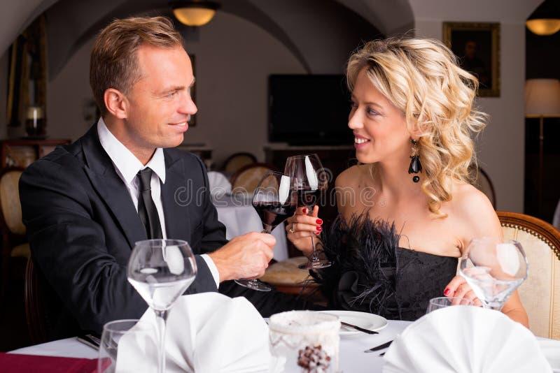Par som har en beröm i restaurang royaltyfri bild