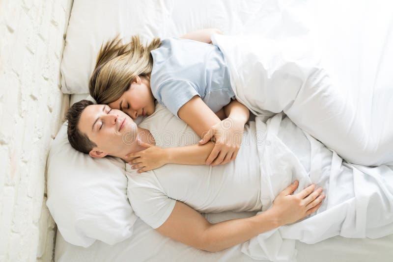 Par som har ett Nap Together On Bed At hem arkivfoton