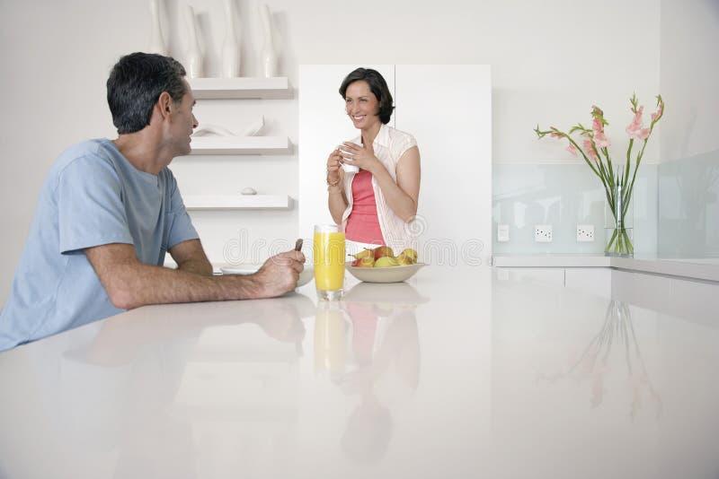 Par som har frukosten på kökbänken royaltyfri foto