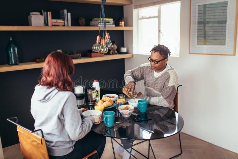 Par som har frukosten tillsammans hemma royaltyfri bild