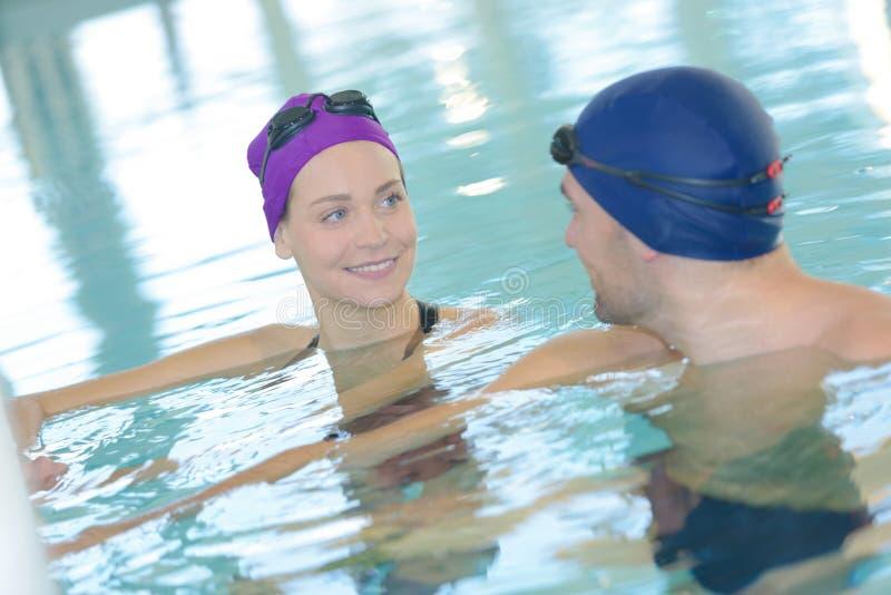 Par som har gyckel i simbassäng royaltyfri foto