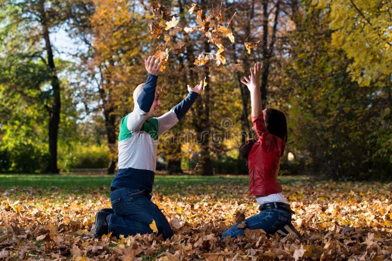 Par som har gyckel med Autumn Leaves In Garden arkivfoto