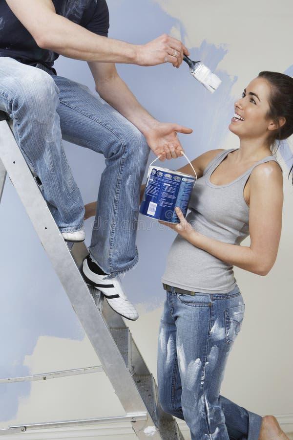 Par som har gyckel, medan måla det Unrenovated huset royaltyfri bild