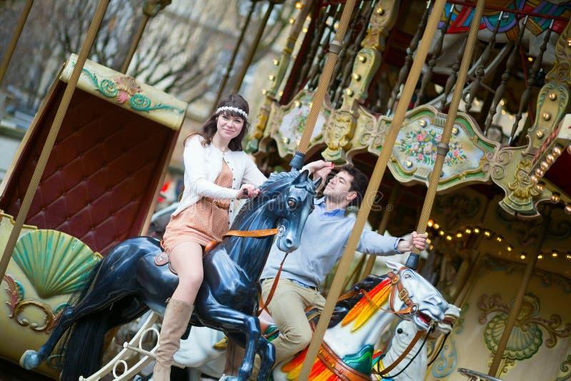 Par som har gyckel på karusell arkivfoto