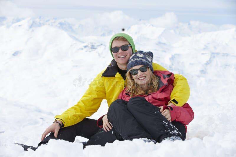 Par som har gyckel skidar på, ferie i berg royaltyfri foto