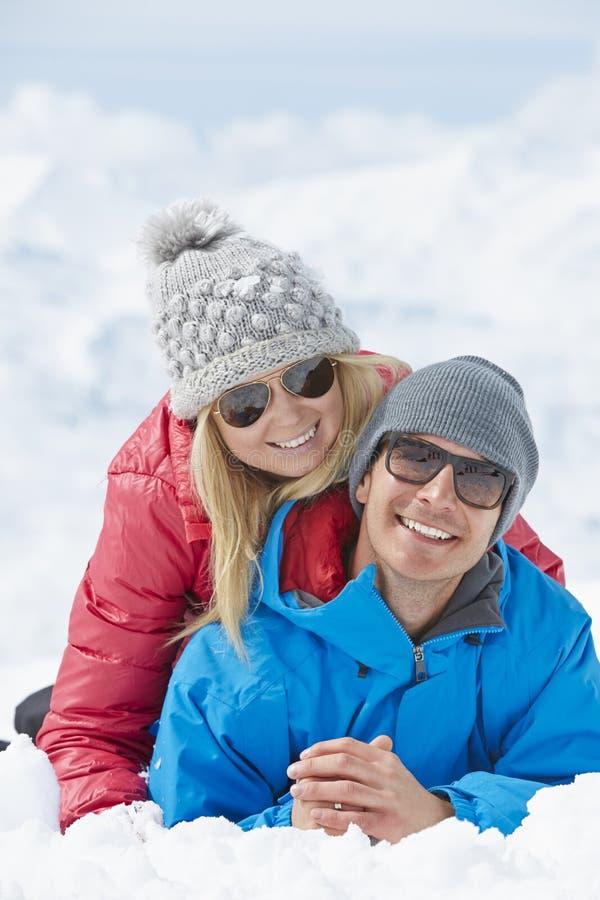Par som har gyckel skidar på, ferie i berg fotografering för bildbyråer