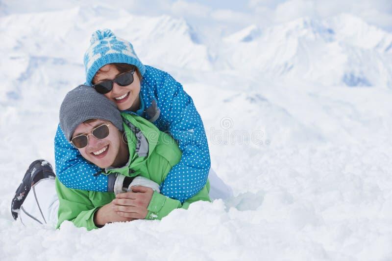 Par som har gyckel skidar på, ferie i berg royaltyfria bilder