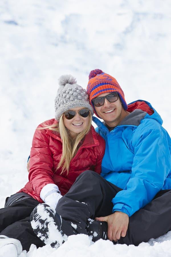 Par som har gyckel skidar på, ferie i berg royaltyfri fotografi