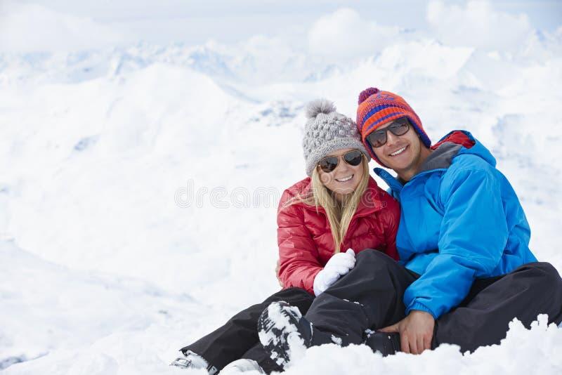 Par som har gyckel skidar på, ferie i berg arkivfoto