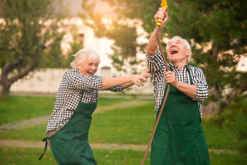 Par som har gyckel, vattenslang arkivfoton