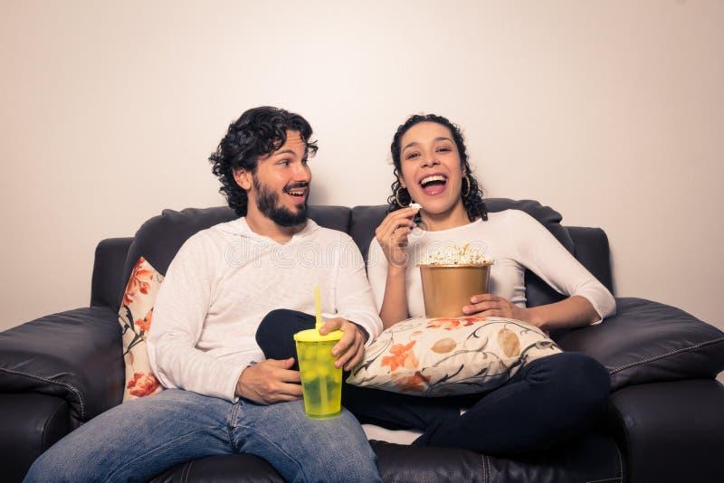 Par som har hållande ögonen på television för gyckel som strömmar Film och serie arkivbild