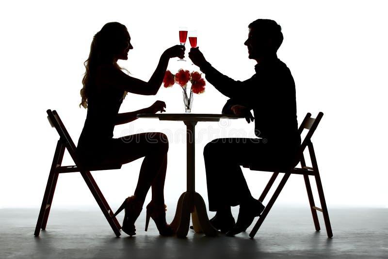 Par som har matställen med vinexponeringsglas på tabellen arkivfoto