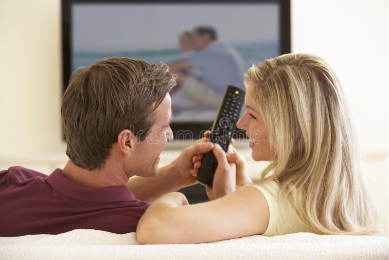 Par som hemma håller ögonen på Widescreen TV royaltyfri bild