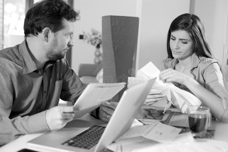 Par som hemma kontrollerar oroade räkningar royaltyfri foto
