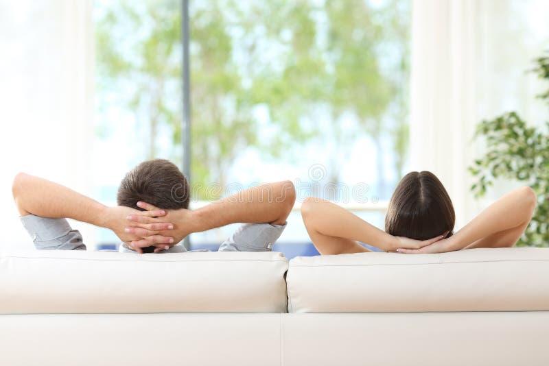 Par som hemma kopplar av på en soffa royaltyfri fotografi