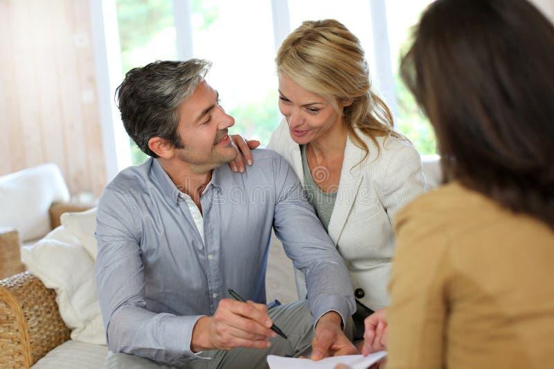 Par som hemma möter den finansiella rådgivaren royaltyfri foto